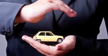 Two hands facing each other, protect a yellow car.