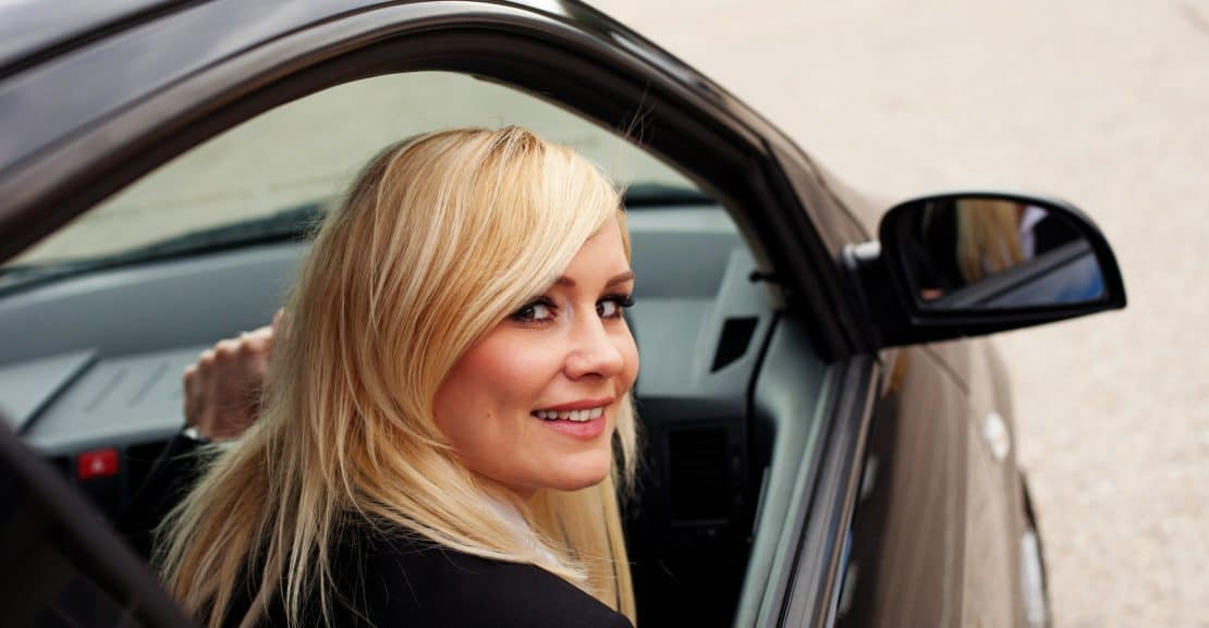 Attractive blonde female driver test driving a car
